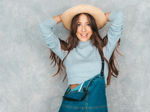 Portrait of young beautiful woman looking  . trendy girl in casual summer overalls clothes and hat. Free Photo