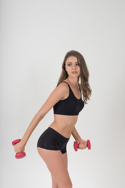Portrait of young beautiful woman making physical exercises with dumbbells Free Photo