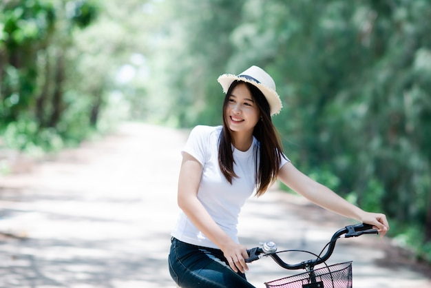 Portrait of young beautiful woman riding a bicycle in a park. Free Photo