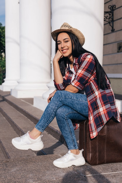 Portrait of young beautiful woman sitting on luggage bag looking at camera Free Photo