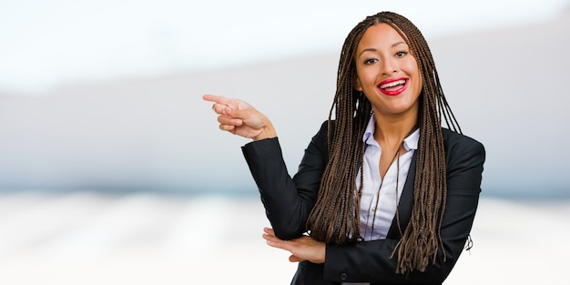 Portrait of a young black business woman pointing to the side, smiling surprised presenting something, natural and casual Premium Photo