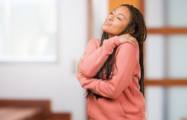 Portrait of a young black woman wearing braids proud and confident, pointing fingers, example to follow, concept of satisfaction, arrogance and health Premium Photo