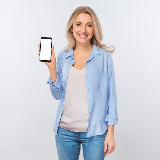 Portrait of a young blonde woman looking at camera showing mobile phone with blank white screen Free Photo