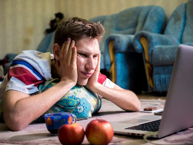 Portrait of young bored man lying in front of the laptop Premium Photo