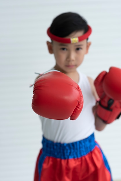 Portrait of young boy boxer in red boxing gloves Premium Photo