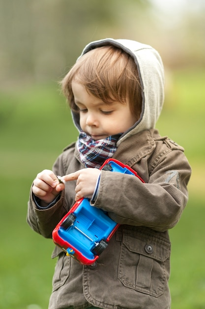 Portrait of young boy checking a flower Free Photo