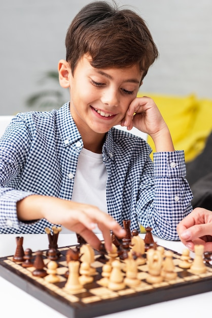 Portrait of young boy playing chess Free Photo