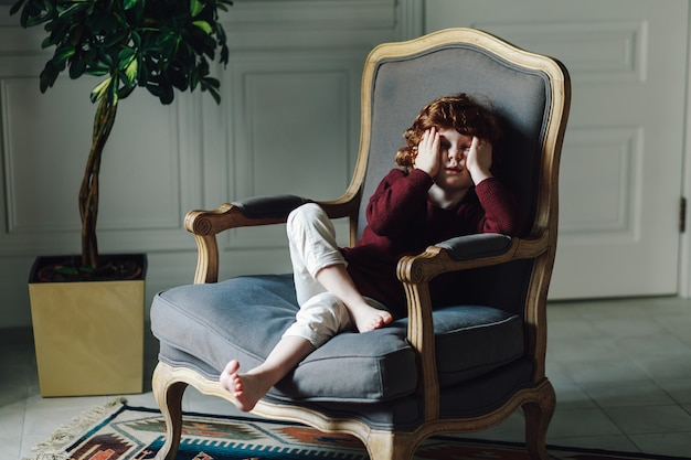 Portrait of a young boy sitting in the armchair and leaning on his hand Premium Photo