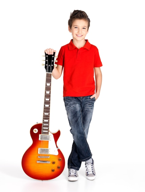 Portrait of young boy with electric guitar - isolated on white wall Free Photo