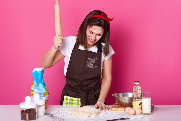 Portrait of young brunette stressed female working in kitchen whole day, preparing homemade pastry, looks tired. beats on dough with wooden rolling pin with anger isolated on rose. Free Photo