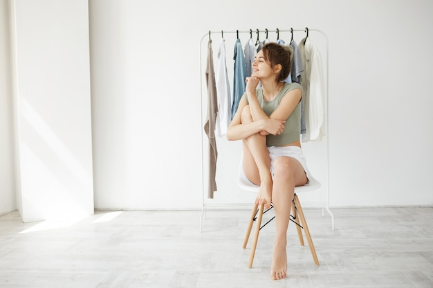 Portrait of young brunette woman smiling looking in side sitting on chair over hanger wardrobe and white wall. Free Photo
