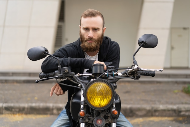 Portrait of young brutal man sitting on motorcycle outdoors Free Photo