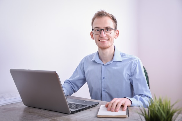Portrait of young  business man sitting at his desk desktop laptop technology in the office.internet marketing, finance, business concept Premium Photo
