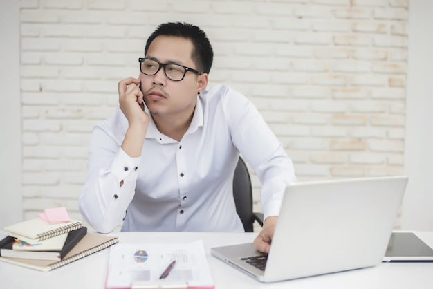 Portrait of young business man sitting at his desk Free Photo