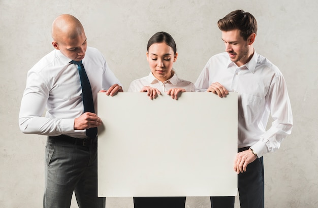 Portrait of young business people looking at big blank placard standing against grey wall Free Photo
