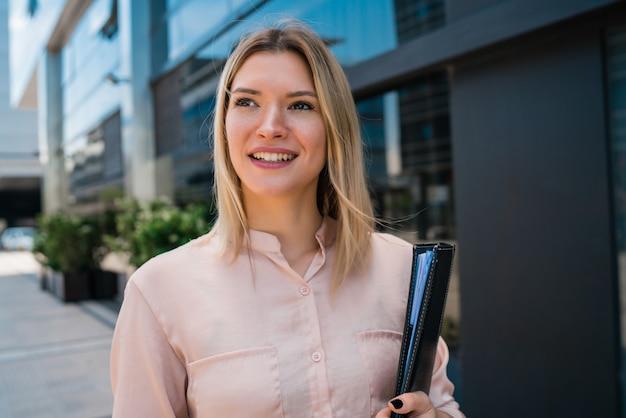 Ritratto di giovane donna d'affari in piedi al di fuori degli edifici per uffici. concetto di affari e successo. Foto Gratuite