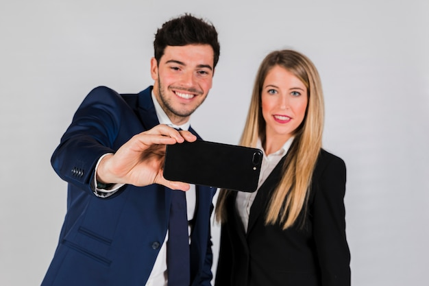 Portrait of a young businessman and businesswoman taking selfie on mobile phone against grey background Free Photo