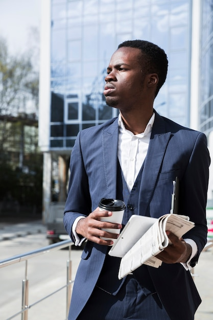 Portrait of a young businessman holding digital tablet; newspaper and disposable coffee cup Free Photo