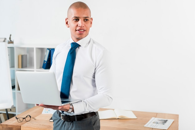 Portrait of a young businessman holding an open laptop in hand looking away Free Photo