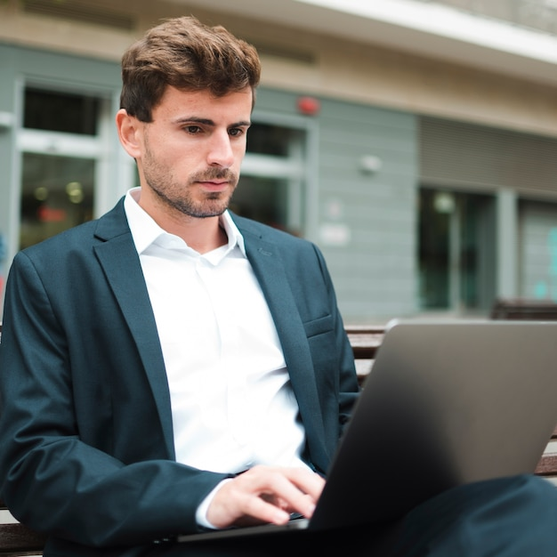 Portrait of a young businessman sitting outdoors using laptop Free Photo