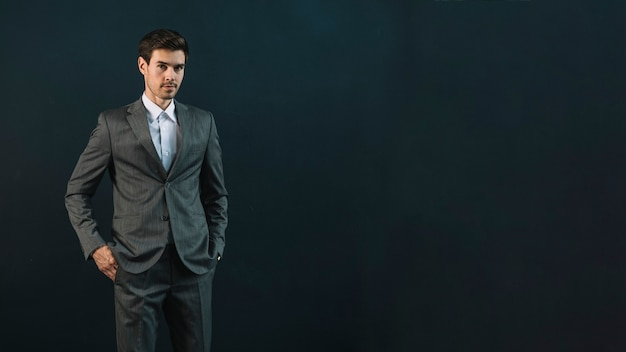 Portrait of a young businessman standing against dark background Free Photo