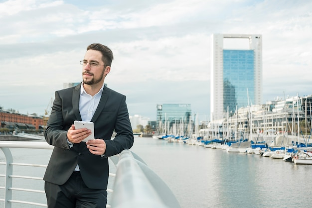 Portrait of a young businessman standing near the harbor holding mobile phone in hand looking away Free Photo