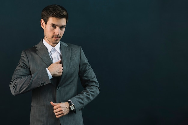 Portrait of young businessman in suit standing against black background Free Photo