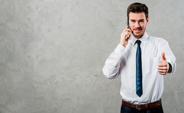 Portrait of a young businessman talking on mobile phone showing thumb up sign against concrete grey wall Free Photo