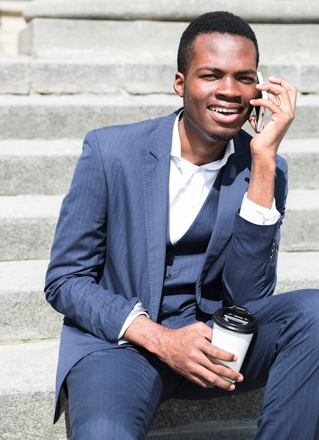 Portrait of a young businessman talking on steps holding disposable coffee cup Free Photo