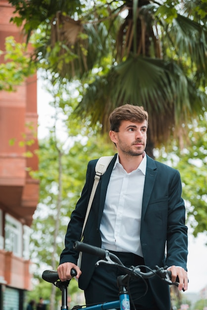 Portrait of a young businessman with his bicycle looking away Free Photo