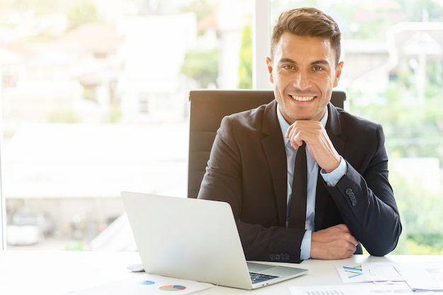 Portrait of young businessman working in office with smile ...