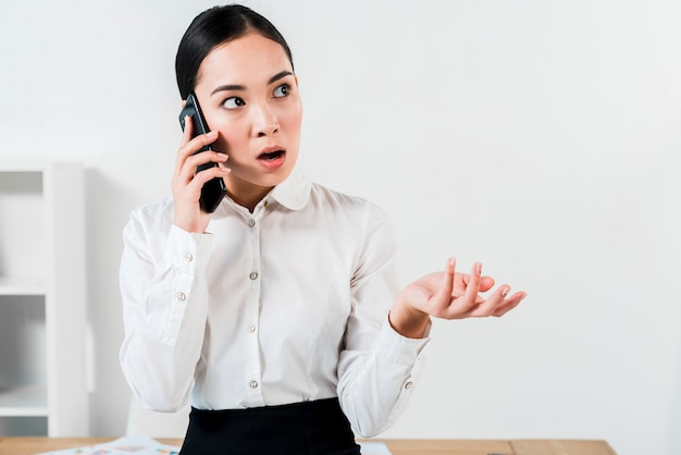 Portrait of a young businesswoman arguing on mobile phone gesturing Free Photo