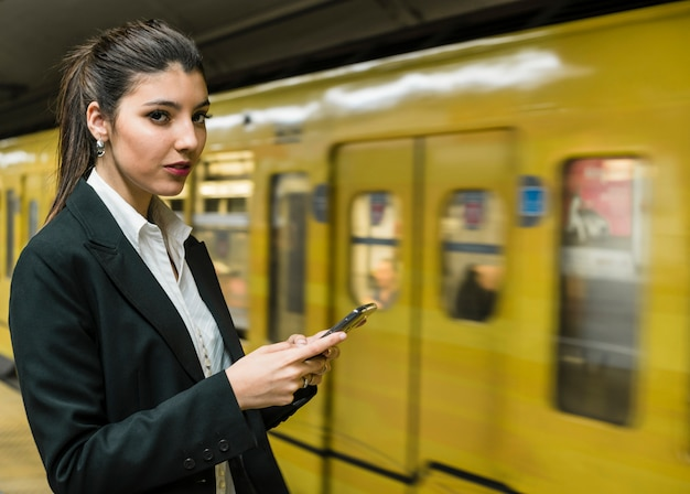Portrait of a young businesswoman holding mobile in hand looking away Free Photo