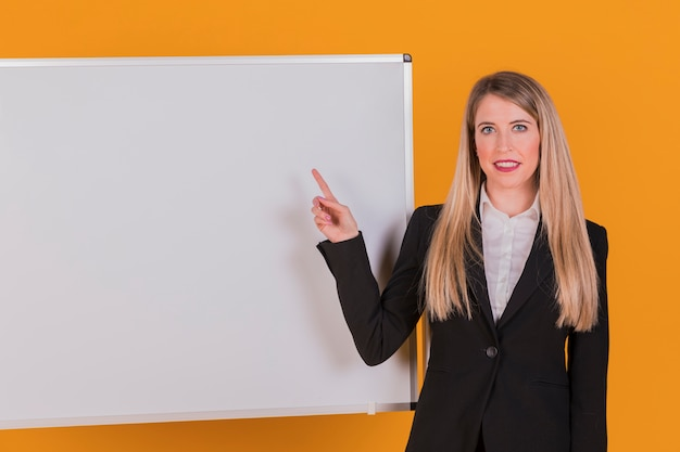 Portrait of a young businesswoman pointing her finger on whiteboard against an orange background Free Photo