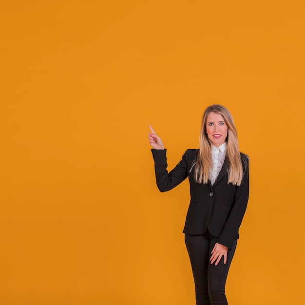 Portrait of a young businesswoman pointing his finger on an orange background Free Photo