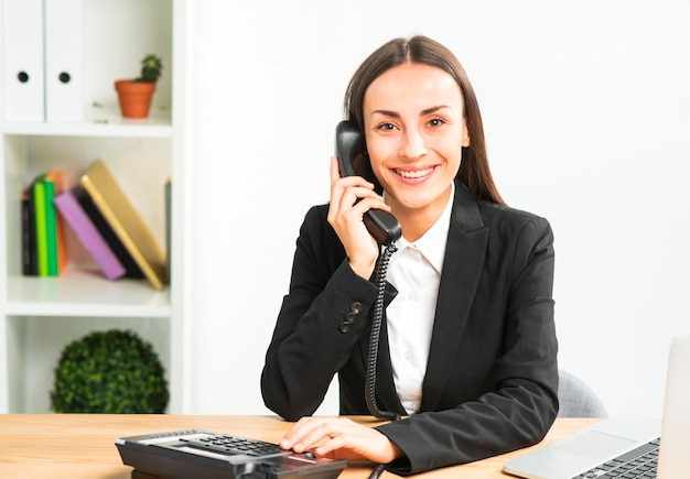 Portrait of a young businesswoman talking on telephone looking at camera Free Photo