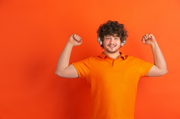 Portrait of young caucasian man with bright emotions on orange studio Free Photo