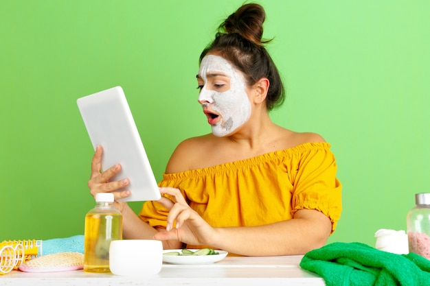 Portrait of young caucasian woman in beauty day, skin and hair care routine. female model making selfie, vlog or videocall while applying facial mask. selfcare, natural beauty and cosmetics concept. Free Photo