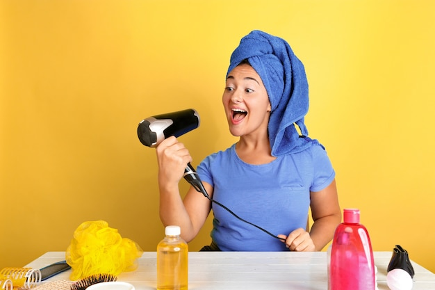 Ritratto di giovane donna caucasica nella sua routine di cura di bellezza, pelle e capelli. modello femminile con cosmetici naturali che applicano crema e oli per il trucco. cura del viso e del corpo, concetto di bellezza naturale. Foto Gratuite