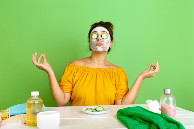 Portrait of young caucasian woman in her beauty day, skin and hair care routine. female model with natural cosmetics applying facial mask for make up. body and face care, natural beauty concept. Free Photo