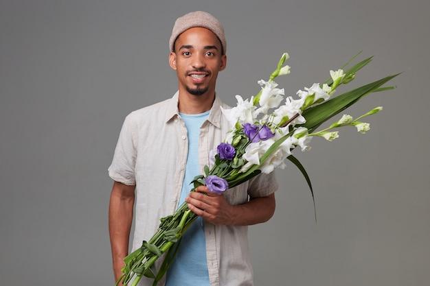 Ritratto di giovane ragazzo attraente allegro con cappello grigio, tiene un mazzo di fiori tra le mani, guarda la telecamera con espressione felice e sorridente, si leva in piedi sopra backgroud grigio. Foto Gratuite
