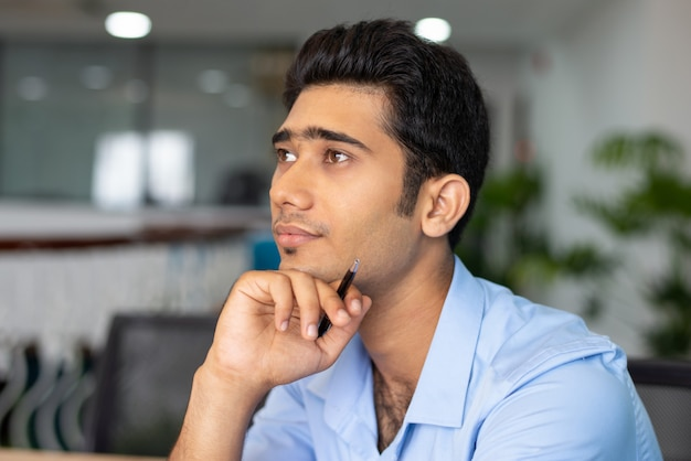 Portrait of young concentrated businessman or student in office Free Photo
