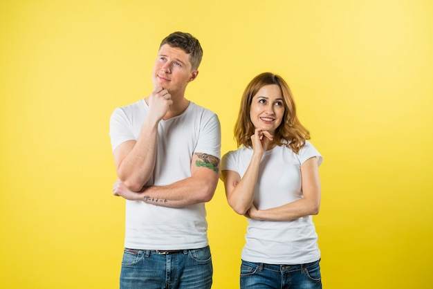 Portrait of a young couple daydreaming against yellow background Free Photo