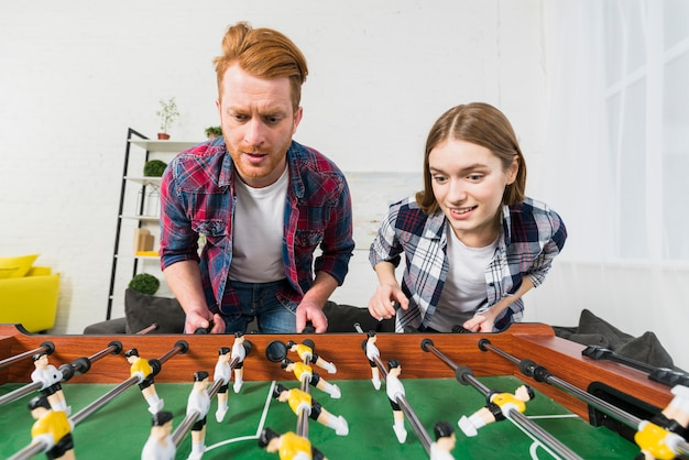 Portrait of young couple enjoying playing the soccer game at home Free Photo
