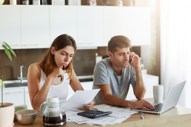 Portrait of young couple: female reading attentively document and male sitting in front of open laptop and chatting with business partner over smart phone, being busy with making financial report Free Photo