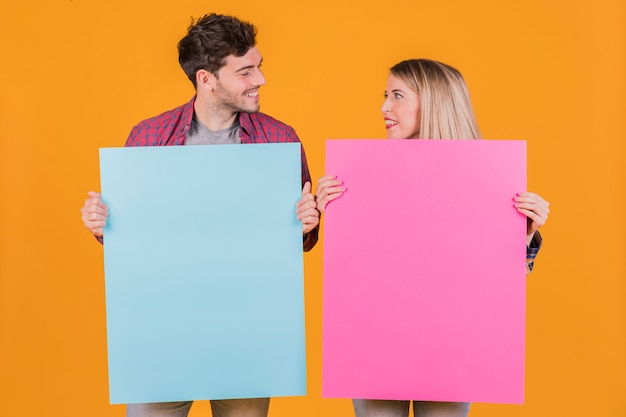 Portrait of a young couple holding blue and pink placard against an orange background Free Photo
