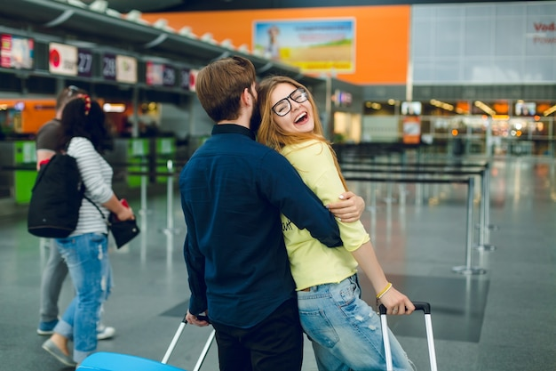 Portrait of young couple hugging in airport. she has long hair, yellow sweater, jeans and smiling to the camera. he has black shirt, pants and suitcase near. view from back. Free Photo
