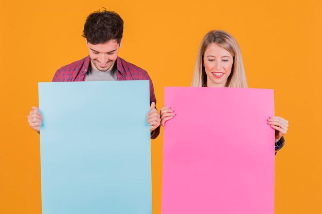 Portrait of a young couple looking at blue and pink placard against an orange backdrop Free Photo