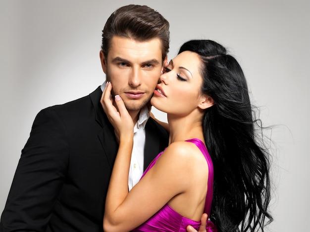 Ritratto di giovane coppia innamorata in posa in studio vestito con abiti classici Foto Gratuite