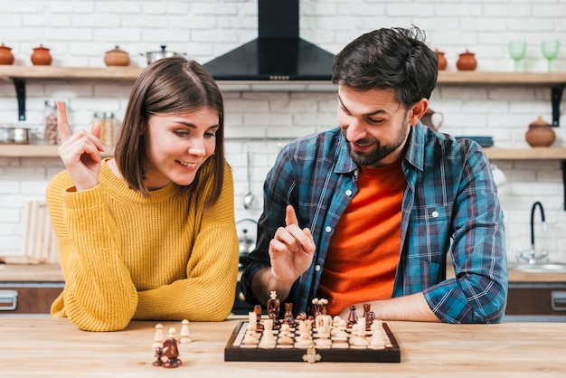 Portrait of a young couple playing the chess in the kitchen Free Photo